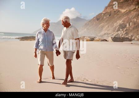 Älteres Rentnerehepaar Strand entlang gehen Hand in Hand - Stockfoto
