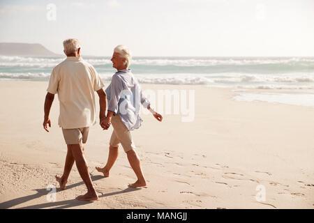 Ansicht der Rückseite des Senior Paar am Strand entlang zu laufen Hand in Hand - Stockfoto