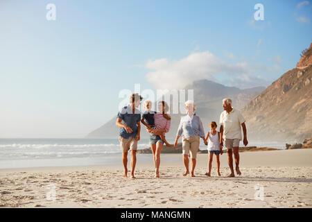 Multi-Generation Familie im Urlaub am Strand entlang zu laufen zusammen - Stockfoto