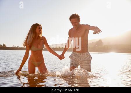 Junge weiße Paar Hände halten in einem See bei Sonnenuntergang - Stockfoto