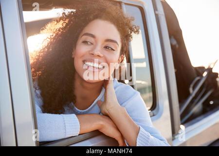Junge Frau aus dem offenen Fenster eines Autos suchen - Stockfoto