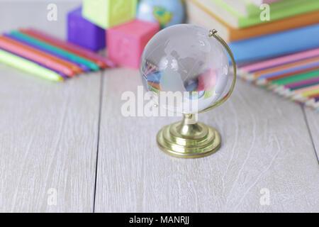 Glas Kugel und Schulmaterial auf hölzernen Hintergrund. Foto mit Kopie Raum - Stockfoto
