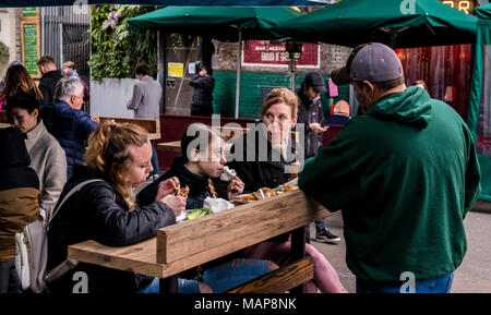 Familie Essen auf Holztisch, Borough Market, London, England, Großbritannien - Stockfoto