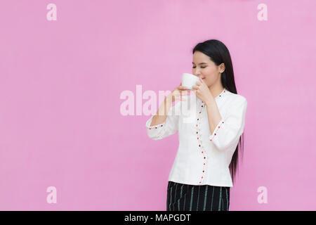 Portrait schöne asiatische Mädchen in traditionellen thailändischen Kleid und halten Kaffee Tasse auf rosa Hintergrund isoliert. Baumwolle Kleid - Stockfoto