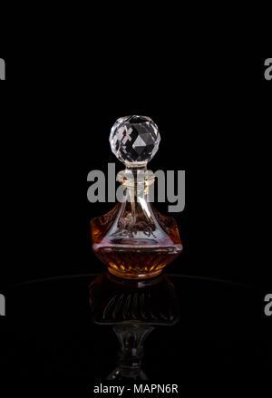 Nahaufnahme von traditionellen luxuriösen arabischen Oud Öl Parfüm in einem wunderschönen handgemachten Klarer Kristall Glas Glas Flasche und Glas Dropper isoliert auf Schwarz - Stockfoto