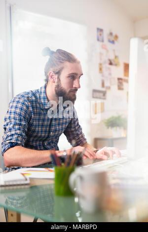 Junger Mann an seinem Schreibtisch vor dem Computer sitzen - Stockfoto