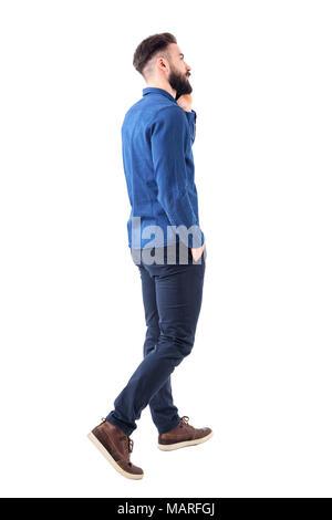 Rückansicht der jungen Elegante Smart Casual business Mann am Telefon gehen und oben zu schauen. Voller Körper auf weißem Hintergrund. - Stockfoto