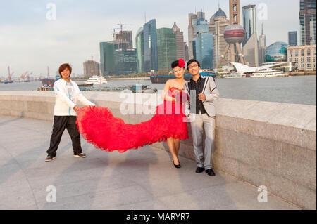 Junge frisch vermählte Paar mit Fotos, auf den Bund gegen die Skyline der Stadt Shanghai, China - Stockfoto