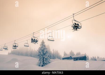 Skifahrer und Snowboarder unterwegs auf einem Sessellift in Morzine Skigebiet in Frankreich. Split getönten Farben Behandlung.