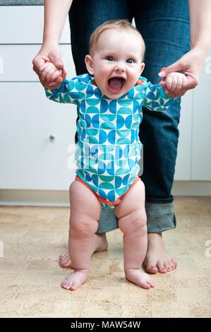 Eine Frau, die ihre sechs Monate alte Tochter stand zu helfen. - Stockfoto