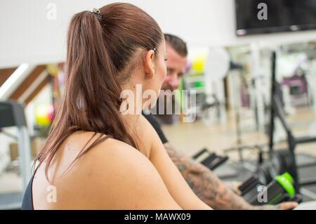 Nachdenkliche Frau, die in einer Turnhalle neben einem tätowierten Mann - Stockfoto