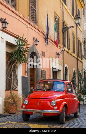 Eine ikonische alten roten Fiat 500 in einer gepflasterten Straße in Rom, Italien, außerhalb eines Gebäudes unter italienischer Flagge geparkt. - Stockfoto