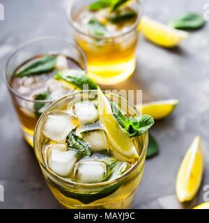 Ein paar Glas Gläser mit einem kalten Kaffee mit Eis, Minze und Zitrone auf grauem Beton Hintergrund. Im Sommer Kühlung trinken - Stockfoto