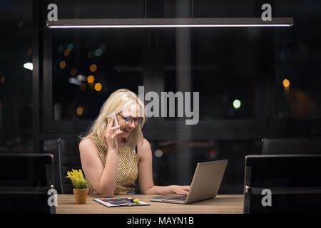 Junge schöne kaukasische Frau auf Laptop im modernen Büro Überstunden - Stockfoto