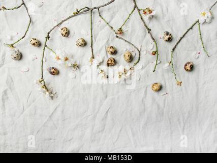 Ostern Hintergrund. Flachbild-lay von Ausschreibung Frühling Mandelblüte Blumen auf den Ästen und Wachteleier in Hellgrau Leinentuch, Ansicht von oben, kopieren Spa - Stockfoto
