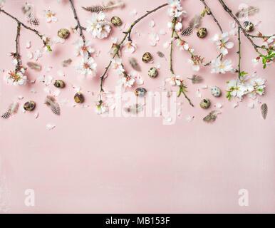Ostern Hintergrund. Flachbild-lay von Ausschreibung Frühling Mandelblüte Blumen auf Ästen, Federn und Wachteleier über Rosa Leinen, Ansicht von oben - Stockfoto