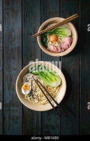 Satz von asiatischen Gericht udon Nudeln mit gekochtem Ei, Sesam, Pilze, boc Choy, sous vide Schweinefleisch serviert in Keramik Schalen mit Stäbchen über dunkle Woo - Stockfoto