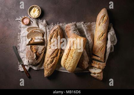 Vielfalt der Laibe frisch gebackene artisan Roggen-, Weiß- und Vollkornbrot auf Leinen mit Butter, mit rosa Salz und vintage Messer über Dunkelbraun Textur