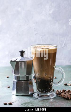 Fizzy Eiskaffee Espresso mit Milch, Kaffeemaschine und gerösteten Bohnen um über Grau Grün Textur Tabelle. Moderne trinken. Platz kopieren - Stockfoto