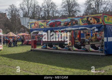 Die Menschen genießen die Fahrgeschäfte auf der Kirmes an einem hellen und sonnigen Frühling Tag nachmittag in Shrewsbury, Shropshire, West Midlands - Stockfoto