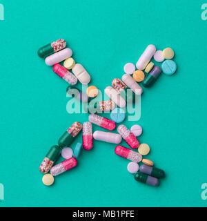 Pillen, die in der Form eines Kreuzes oder X auf einem grünen Hintergrund. Konzeptionelle für die pharmazeutische Produktion. - Stockfoto
