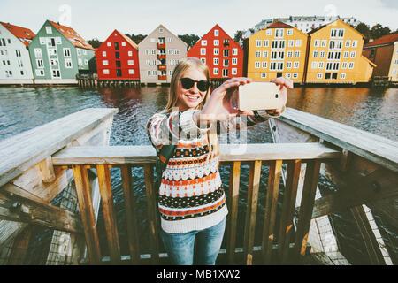 Glücklich lächelnde Frau unter selfie Reisen in Stadt Trondheim Norwegen Urlaub Wochenende Lifestyle Fashion outdoor skandinavische Häuser Wahrzeichen archit - Stockfoto