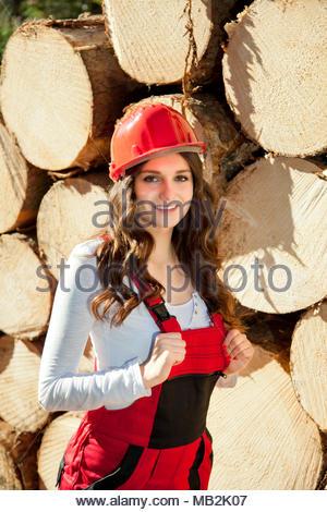 Junge schöne Frau stand vor der Deponierung von Rundholz und mit einem Lächeln in die Kamera zu schauen. Sie trägt rote Arbeiten overalls Helm. - Stockfoto