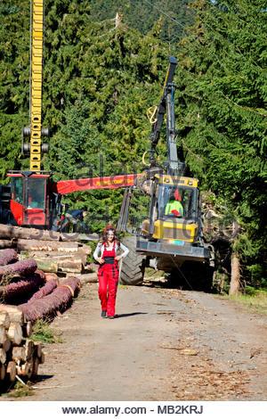 Jungen Wald Techniker stand vor der forstwirtschaftliche Maschinen für die Protokollierung. Sie trägt rote Arbeitskleidung und einen Helm. Maschine. - Stockfoto