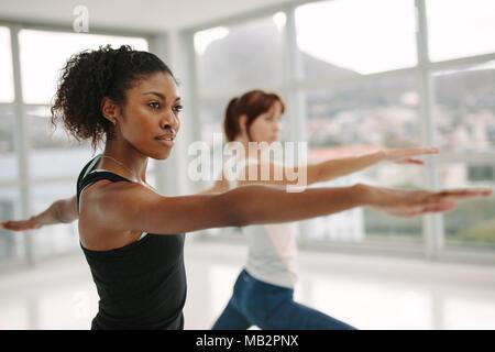 Afrikanische Frauen Fitness Trainer, Yoga im Krieger darstellen. Frau recken ihre Arme beim Yoga Klasse. Virabhadrasana. - Stockfoto