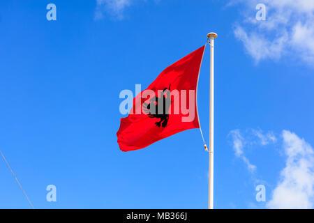 Albanien Flagge. Albanische Flagge an einem Fahnenmast winken in der entgegengesetzten Richtung auf einem blauen Himmel Hintergrund - Stockfoto