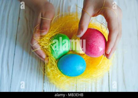 Bunte Ostereier im weißen Holz- Hintergrund in Kinderhände. - Stockfoto