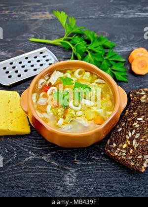 Minestrone mit Fleisch, Sellerie, Tomaten, Zucchini, Kohl, Erbsen, Karotten und Pasta in einem irdenen Schüssel, Käse, reibe auf Schwarz hinterg - Stockfoto
