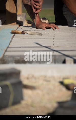 Arbeitnehmer mit Tools, die bei der Verlegung Beton Ziegel an einem sonnigen Tag - Stockfoto