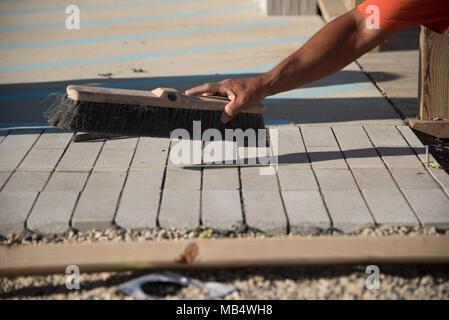 Nahaufnahme des Arbeitnehmers fegen Beton Ziegel nach der Verlegung auf Sand Schicht - Stockfoto