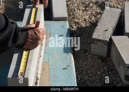 Nahaufnahme der Arbeitnehmer messen brick Stücke mit Klebeband vor dem Verlegen - Stockfoto