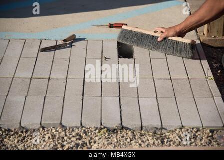 Nahaufnahme der Hand Reinigung Beton Ziegel mit Bürste - Stockfoto