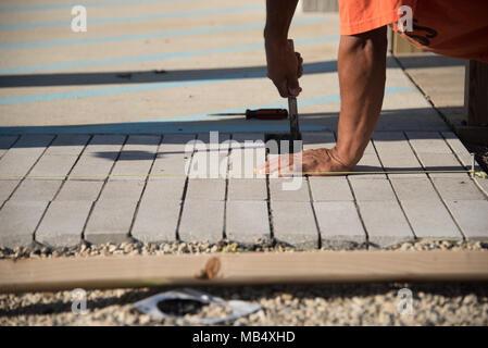 Nahaufnahme des Arbeitnehmers zur Festlegung konkreter Ziegel an einem sonnigen Tag - Stockfoto