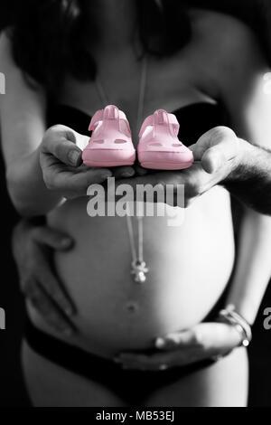 Schwarz und Weiß mit farbigen Details, eine schwangere Frau und die Zukunft Papa halten zwei Rosa neugeborenen Schuhe in Richtung der Kamera - Stockfoto