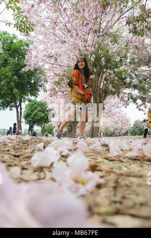 Asiatische reisende Thai Menschen zu Fuß reisen und rosa Trompete Blume für Foto im Garten in Kamphaeng Saen besuchen Sie am 17. April 2017 in Nakhon Pathom - Stockfoto