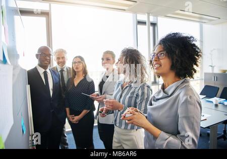 Vielfältige Gruppe von konzentrierter Arbeit und Kollegen eine Planung und Strategie treffen sich gemeinsam auf einem Whiteboard in einem hellen modernen Büro - Stockfoto