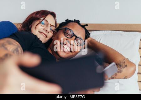 Fröhliche gemischtrassiges Paar zusammen im Bett liegen und unter selfie. Lächeln, Mann und Frau, die selfie mit Handy. - Stockfoto