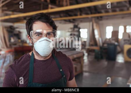 Junge woodworker mit Schutzkleidung in seiner Werkstatt - Stockfoto