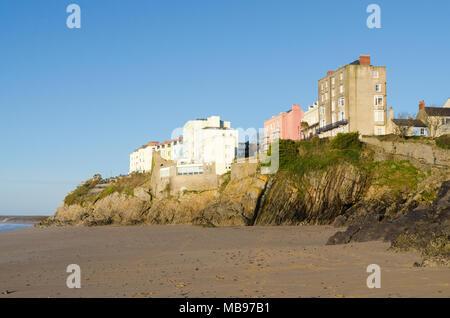 Bunte Häuser mit Blick auf Castle Beach, Tenby am frühen Morgen Sonnenschein - Stockfoto