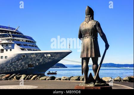 Leiv Erikson statue sieht Seaward gegen den blauen Himmel Hintergrund. Figur aus Bronze mit Schwert und Axt, stehend durch Bogen von großen Kreuzfahrtschiff - Stockfoto