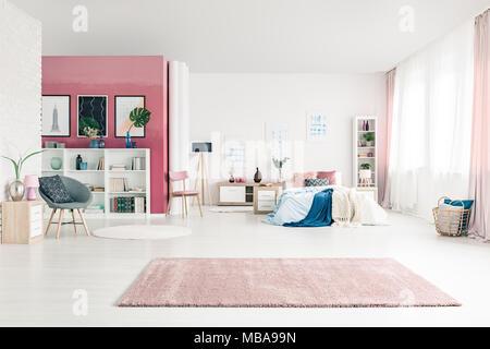 Raum Schlafzimmer Innenraum mit großer Teppich öffnen, gemütliches Bett, rosa und weiße Wände, Stühle, Poster, Korb, rosa Vorhängen und Bücherregale - Stockfoto