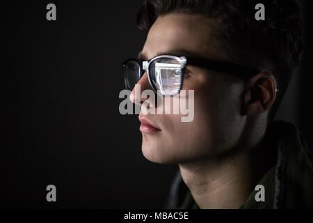 Augen der ernsthaften jungen Mann in Schwarz rim Gläser mit seinem Tablet Computer. Bildschirm und Finger in das Glas reflektiert - Stockfoto