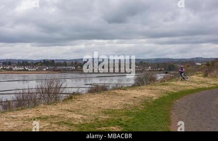 Ein einsamer Radfahrer eine Pause auf einem grasbewachsenen Bank auf der Riverside Nature Trail mit Blick auf invergowrie Dorf am Stadtrand von Dundee, Angus, Scotlan - Stockfoto