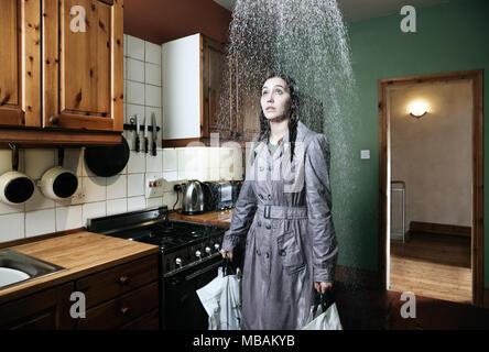 Frau, die in der Küche unter der Dusche von Regen, drinnen - Stockfoto