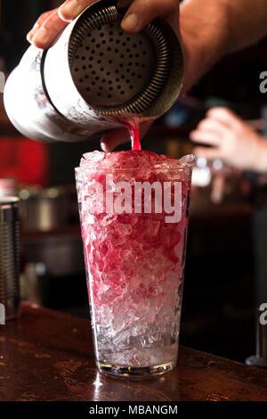 Nahaufnahme von einem Barkeeper aus einem rotem Cocktail, Gießen in das Glas mit crushed Ice.
