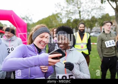 Läuferin Freunden über Smart Phone an der Nächstenliebe laufen im Park - Stockfoto